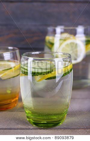 Fresh water with lemon and cucumber in glassware on wooden background