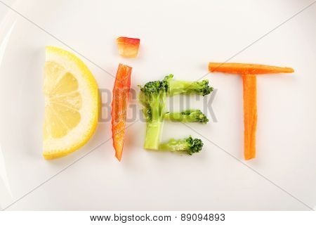 Word DIET made of sliced vegetables on white plate background