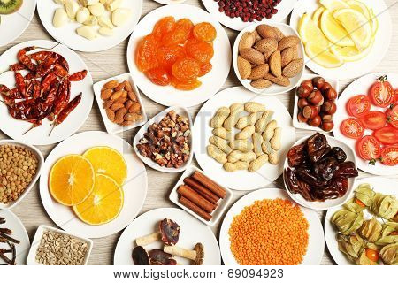 Different products on saucers on wooden table, top view