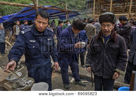 Chinese Policeman On A Rural Celebration Eating Using Wooden Chopsticks.