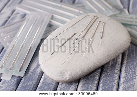 Acupuncture needles on wooden table with spa stones, closeup