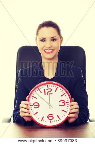 Happy businesswoman holding a big clock