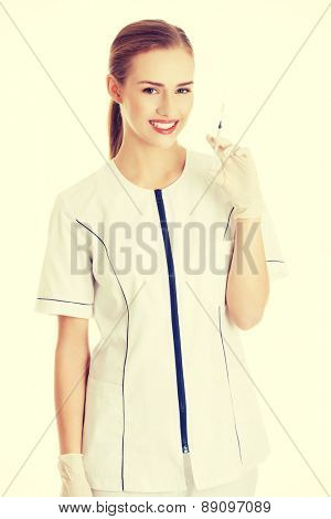 Young beautiful dentist holding a syringe