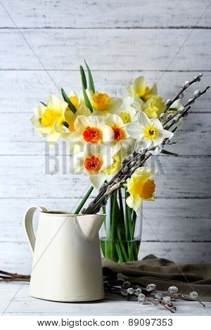 Fresh narcissus flowers with willow sprigs on wooden background