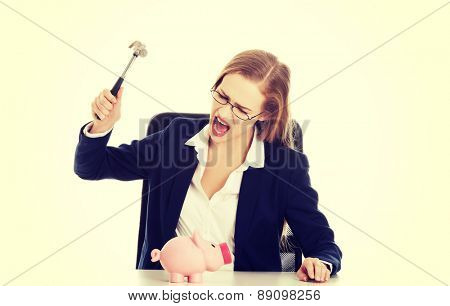 Young businesswoman breaking a piggybank
