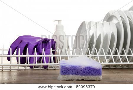 Plates in foam with gloves and cleanser on table close up