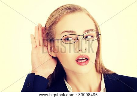 Young beautiful blond businesswoman overhears
