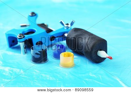 Tattoo machine and colorful ink, close-up, on blue background