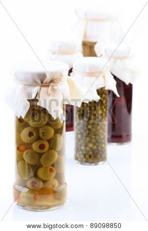 Pickled vegetbles in jars on white background