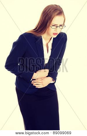 Blonde businesswoman with strong stomachache