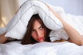 stock photo of lie  - Female lying on bed and closing her ears with pillow - JPG
