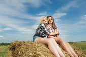 pic of bundle  - Portrait of leggy blonde and brunette girls are posing on bundle of straw - JPG
