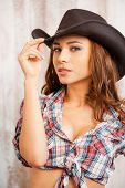 foto of cowgirls  - Beautiful young cowgirl adjusting her hat and looking at camera while standing against the wooden background - JPG