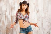 image of cowgirls  - Beautiful young cowgirl gesturing and looking at camera while standing against the wooden background - JPG