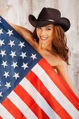 stock photo of cowgirls  - Beautiful young shirtless cowgirl wearing hat and covering herself by American flag while standing against the wooden background - JPG