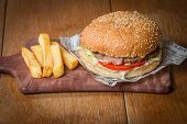 pic of beef-burger  - Delicious burger with beef tomato cheese and lettuce on paper and fries on wooden table - JPG