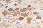 picture of fifties  - Closeup of different coins over fifty notes background - JPG