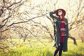 image of cloak  - Portrait of a beautiful redhead women in cloak and hat with camera in blossom apple tree garden in spring time on sunset.