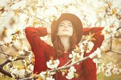 pic of redhead  - Portrait of a beautiful redhead women in red sweater and hat in blossom apple tree garden in spring time on sunset - JPG