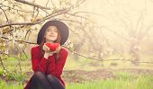 foto of redhead  - Portrait of a beautiful redhead women in red sweater and hat with cup in blossom apple tree garden in spring time on sunset - JPG