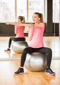 picture of pregnancy exercises  - Young pregnant woman doing exercise using a fitness ball - JPG
