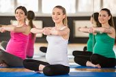 picture of pregnancy exercises  - Group of young pregnant women are doing relaxation exercise on exercise mat - JPG