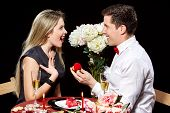 picture of marriage proposal  - Man proposing marriage to a surprised woman on black background - JPG