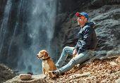 pic of waterfalls  - Man With his Dog Sitting Near Waterfall - JPG