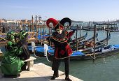stock photo of carnivale  - three venice carnivale party goers welcome you to the grand canal in italy - JPG