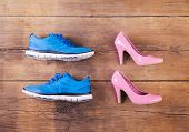 stock photo of pink shoes  - Running shoes and pink court shoes on a wooden floor background - JPG
