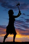 stock photo of cave woman  - a silhouette of a cave woman with her hatchet up in the air - JPG