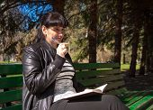 image of black pants  - young beautiful woman in a black leather jacket and black pants sitting on a park bench holding a pen and notebook - JPG