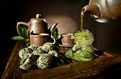 picture of loam  - horizontal photo of the clay teapot tea flow in cup on brown background tea ceremony - JPG