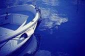 stock photo of outboard engine  - wooden boat by the shore in blue - JPG