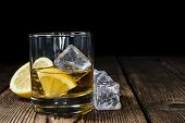 foto of whiskey  - Whiskey with lemon and ice cubes on rustic wooden background - JPG