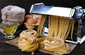 foto of pasta  - Metal pasta maker machine and ingredients for pasta on wooden background - JPG
