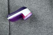 pic of lint  - Wool shaver on wool sweater background - JPG