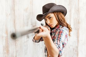 stock photo of cowgirl  - Beautiful young cowgirl aiming her gun at camera while standing against the wooden background - JPG
