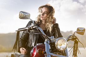 picture of biker  - Biker girl in the  leather jacket on a motorcycle looking at the sunset - JPG