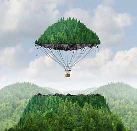 picture of lifting-off  - Imagination concept as a person lifting off with a detached top of a mountain floating up to the sky as a hot air balloon as a metaphor for the power of imagining traveling and dreaming of moving mountains - JPG