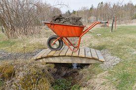 pic of hand-barrow  - Orange wheel barrow full of mud standing on a small bridge - JPG