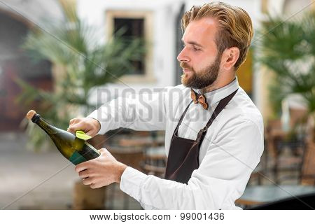 Barman opening bottle with sparkling wine