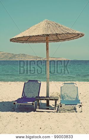 Greece. Kos Island. Two Chairs And Umbrella On The Beach. In Instagram Style Filtered