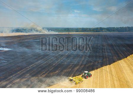 Tractor Harrowing The Field In Fire