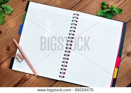 Opened spiral notebook with pencil and sharpener