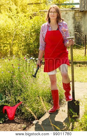 Woman Standing With Shovel In Garden