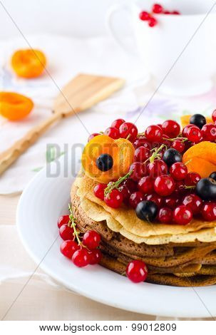 Pancakes with berries and fruits: apricot, red, blackcurrant