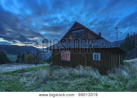 Fantastic evening landscape glowing by sunlight. Dramatic autumn scene with wooden house. Carpathians, Ukraine, Europe.