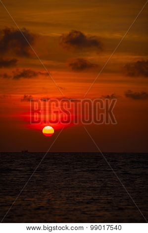 Red Ball Of The Sun Descending Towards The Horizon At Sunset