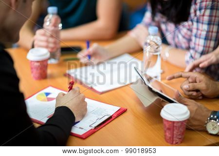 Close up of hands with paperwork and tablet on working table
